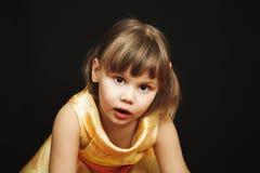 Überraschtes kleines blondes Mädchen im gelben Kleid Stockfotos