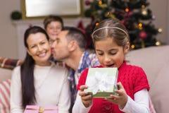 Überraschtes kleines Mädchen, das ein Geschenk öffnet Stockbilder