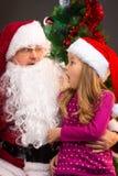 Überraschtes kleines Mädchen, das gefälschte Santa Claus mit gefälschtem Bären betrachtet Stockfoto
