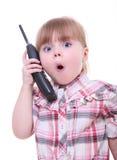 Überraschtes kleines Mädchen, das am Telefon spricht Lizenzfreies Stockfoto