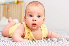 Überraschtes Kleinkind liegt Stockfotografie