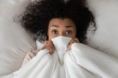 Überraschtes lustiges afrikanisches Mädchen im Bettbedeckungsgesicht mit Decke stockfoto