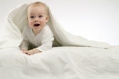 Überraschtes lustiges Kind unter weißer Decke, Atelieraufnahme, lokalisierter, weißer Hintergrund Lizenzfreies Stockfoto