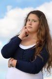 Überraschtes Mädchen betrachtet Kamera auf Himmel Lizenzfreies Stockfoto