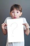 Überraschtes Mädchen, das ein weißes Blatt hält Stockbild
