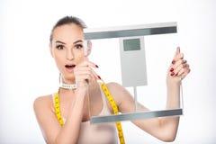 Überraschtes Mädchen, das Ergebnis der Diät darstellt Stockfotos