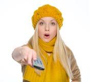 Überraschtes Mädchen, das Fernsehfernbedienung verwendet Stockbild