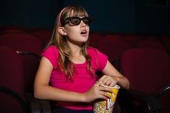 Überraschtes Mädchen, das Gläser 3D beim Essen von Popcorn während des Films verwendet Stockfotografie