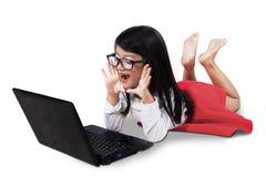 Überraschtes Mädchen, das Laptop betrachtet Stockfotografie