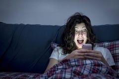 Überraschtes Mädchen, das Smartphone im Bett verwendet Lizenzfreie Stockfotos