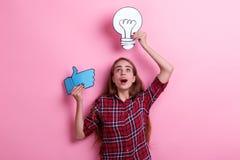 Überraschtes Mädchen, Griffe ein Bild einer Birne und ein Zeichen des Daumens oben und der Blicke auf es lizenzfreie stockfotografie