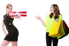 Überraschtes Mädchen mit den Einkaufstaschen, die Frau und ihre Geschenkbox zeigen. Stockfotos
