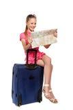 Überraschtes Mädchen mit der Karte, die auf einem Koffer sitzt Lizenzfreies Stockbild