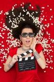 Überraschtes Mädchen mit Gläsern des Kino-3D, Popcorn-Direktor Clapboard Stockfotografie