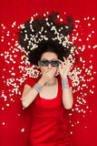Überraschtes Mädchen mit Gläsern und Popcorn des Kino-3D einen Film aufpassend Stockfotografie