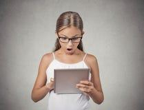Überraschtes Mädchen mit Gläsern unter Verwendung des Auflagencomputers stockfotografie