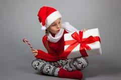 Überraschtes Mädchen mit Weihnachtsgeschenk Stockbild