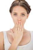 Überraschtes Modell im weißen Kleid, das ihren Mund bedeckend aufwirft Lizenzfreie Stockfotos