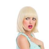 Überraschtes nettes blondes Mädchen, das weg schaut Stockfotos
