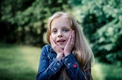 Überraschtes nettes kleines blondes Mädchen am Sommerfeld Stockfotos