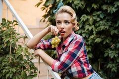 Überraschtes nettes Pin-up-Girl mit Weintraube lizenzfreies stockbild