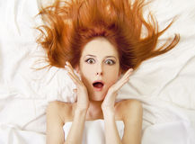Überraschtes red-haired Mädchen im Bett Stockbilder