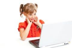 Überraschtes Schulmädchen, das am Notizbuch sitzt Lizenzfreies Stockfoto