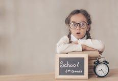 Überraschtes Schulmädchen mit Büchern stockfotografie