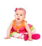 Überraschtes, trauriges kleines Baby in hellem mehrfarbigem festlichem d Lizenzfreie Stockbilder