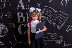Überraschtes und enttäuschtes Schulmädchen, das vor der Tafel als Hintergrund mit einem rosa Rucksack auf ihr zurück steht stockfotografie