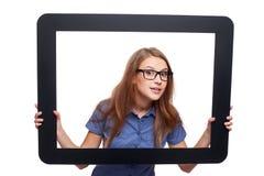 Überraschtes weibliches Lugen aus Tablettenrahmen heraus Stockfotos