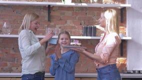 Überraschung auf den Mutter-Geburtstags-, kleinen und erwachsenentöchtern mit Geschenk und Feiertagskuchen mit Kerzen beglückwüns stock footage