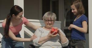 Überraschung für Großmutter-die liebende Familien-Tochter und Enkelin, die Geschenk für alte Oma-sitzendes lächelndes Freien a ve stock video