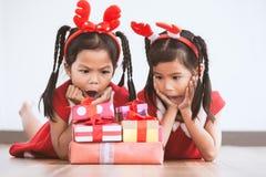 Überraschung mit zwei nette asiatische Kindermädchen mit Geschenkboxen stockbilder