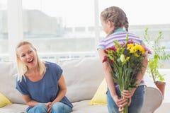 Überraschungsmutter, die versteckenden Blumenstrauß des Mädchens betrachtet Stockfotografie