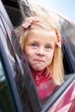Überraschungsstarren des kleinen Mädchens aus dem Auto heraus Lizenzfreie Stockfotos