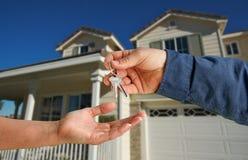 Überreichen der Haus-Tasten vor neuem Haus Lizenzfreie Stockfotografie