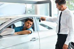 Überreichender Schlüssel Neuwagen des Auto-Verkäufers zum Kunden am Ausstellungsraum Lizenzfreies Stockbild