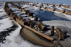 Überreste eines hölzernen Piers auf dem See im Winter Stockbilder