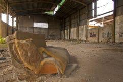 Überreste eines Sofas in einem verlassenen industriellen Lager stockbild