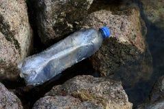 Überschüssige Plastikflasche in dem Fluss, überschüssige Verschmutzung, Abfall-Abfallplastikflaschen leeren sich auf Stein Stockfoto