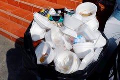 Überschüssiger Schaumbehälter und -plastik, vergeudet Abfallschaum-Essenstablettweiß, das viele auf der schwarzen schmutzigen Pla lizenzfreies stockbild