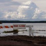 Überschwemmte Straße blockiert mit geschlossenem Zeichen der Straße Stockbilder