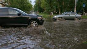 Überschwemmte Straßenautos, die sich langsam in tiefe Pfützen bewegen stock video footage
