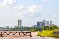 Überschwemmter Arkansas River mit alter Eisenbahn drehte Fußgängerbrücke und 21. Straßenbrücke und Stadtskyline herein lizenzfreies stockfoto