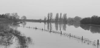 Überschwemmter Fluss über Ackerland Stockbild