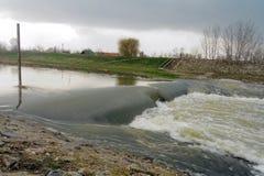 Überschwemmter Fluss mit ländlicher Landschaft Stockbild