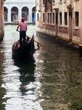 Übersetzende Touristen des Gondolieren mit seiner Gondel in Venedig Lizenzfreies Stockfoto