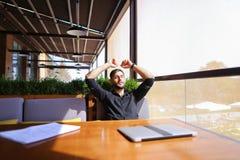 Übersetzer, der Papiere und schließend Laptopdeckel sortiert Stockfoto