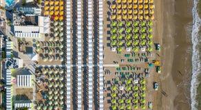 Übersteigen Sie hinunter Brummenvogelperspektive der Regenschirme und der Gazebos auf italienischen sandigen Stränden Riccione, I Lizenzfreies Stockbild